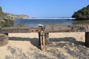 Tempat duduk dari batang pohon kelapa untuk menikmati keindahan Pantai Drini